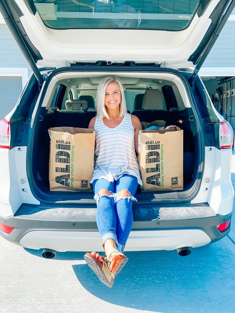 curbside pickup experience with ALDI USA, me pictured in trunk with ALDI bags